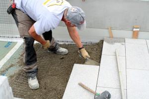 Mitarbeiter beim verlegen von Betonplatten